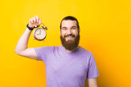 Positive smiling man is holding up an alarm clock.