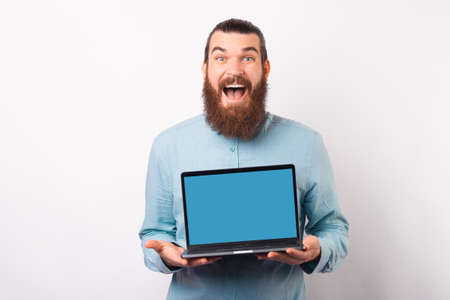 Excited bearded man is showing to the camera his laptop screen.