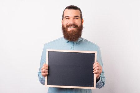 Smiling bearded man is holding a black chalkboard in front of him. Standard-Bild