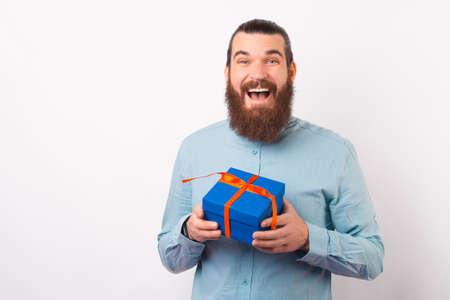 Amazed young man is holding a gift box while smiling at the camera.
