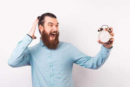 Amazed bearded hipster is looking at the alarm clock he is holding.