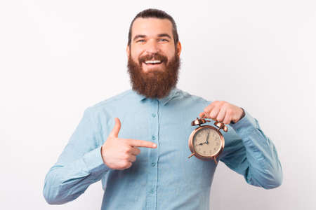 Smiling at the camera bearded man is pointing at an alarm clock.