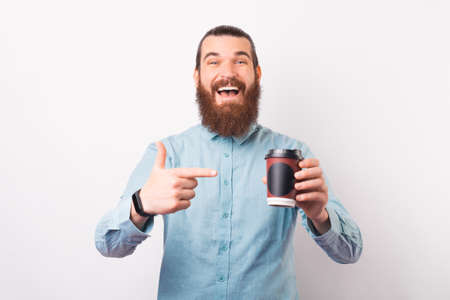 Excited bearded man is pointing at a paper cup of coffee he is holding.