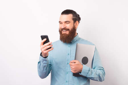 Smiling bearded man is using his phone while holding laptop.