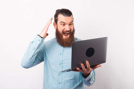 Bearded man is super excited while looking at the laptop. Standard-Bild