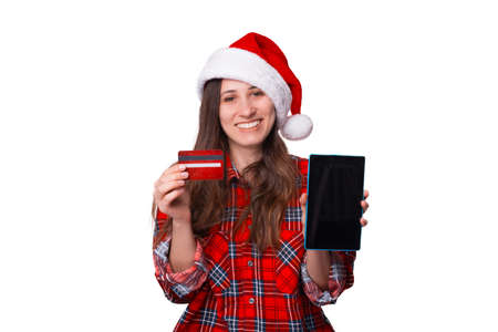 Woman wearing a plaid shirt and Christmas hat holds a card and tablet. Standard-Bild