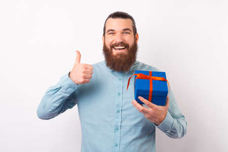 Happy bearded man is showing thumb up while holding a gift box.