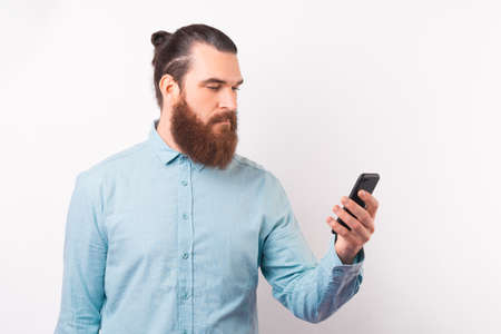 Serious bearded man is looking at the phone he is holding. Standard-Bild