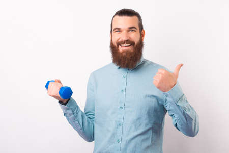 I recommend going to the gym. Bearded man is showing thumb up and holding a dumbbell.