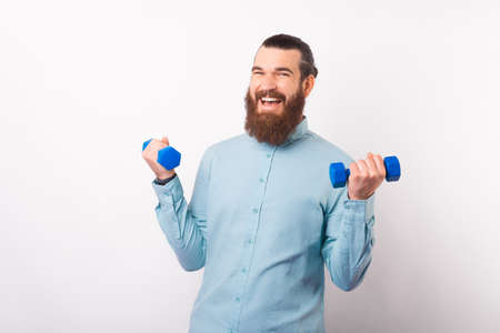 Happy positive man is lifting up some small dumbbells. Standard-Bild