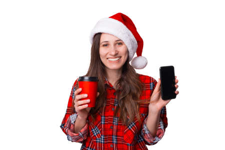 Smiling Christmassy woman is showing the screen of her phone to the camera. Standard-Bild