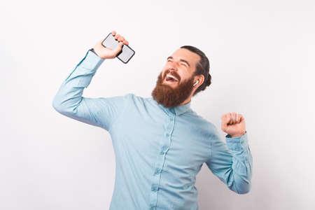 Happy dancing man is enjoying the music he is listening through earphones and his phone