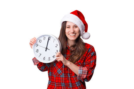 Cheerful woman wearing Christmas hat is holding a wall clock.