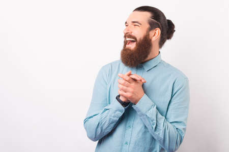 Portrait of a laughing young man holding hands together.