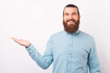 Confident bearded man wearing shirt is presenting you something.
