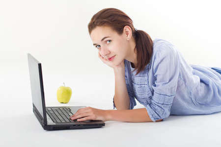 Teen girl, doing homework on the laptop, with green apple besides, for a healthy snack. Studio shot. photo