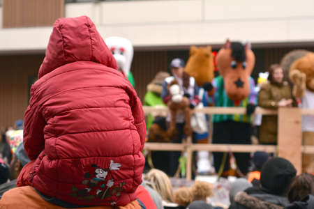 karlsruhe: Karlsruhe, Baden Wuerttemberg, Germany - February 16, 2015: The 300th anniversary of the city of Karlsruhe, annual Carnival and parade, Fasching. Child on his parent shoulders watching the parade. Editorial