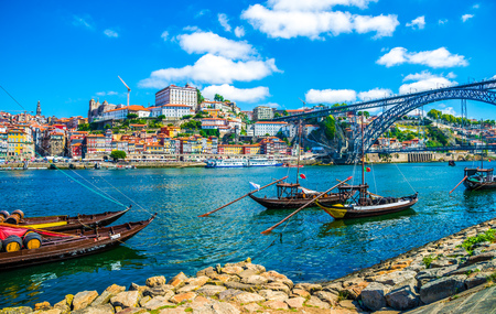 Dom Luis I bridge and traditional boats on Rio Douro river in Porto, Portugal Archivio Fotografico