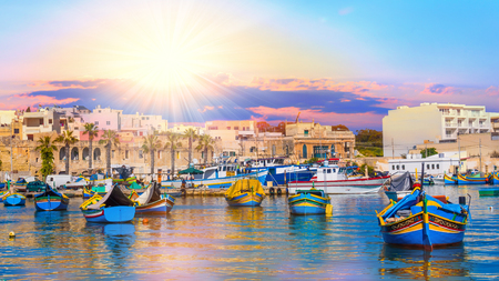 Beautiful panorama of Valletta harbor in Malta, with boats and architecture illuminated by sunset light Stok Fotoğraf
