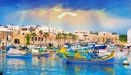 Marsaxlokk village harbor of Malta, illuminate by sunset light