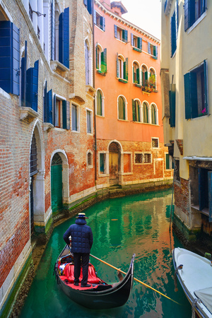 Gondolier on the canal transporting tourists among traditional old house in Venice, Italy