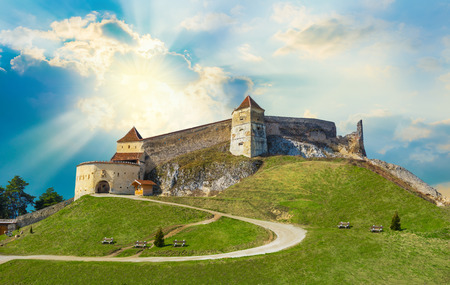 Historic citadel of Transylvania on the hill of Rasnov town illuminated by sunset, in Romania