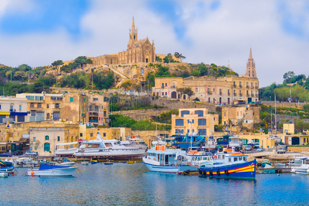 Beautiful cityscape over Gozo island, with medieval architecture and passenger boats on the harbor - Malta