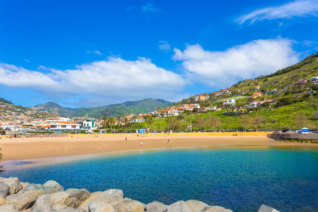 Famous beach of Machico in summer holiday, with sunshine and blue water of the sea in Madeira - Portugal