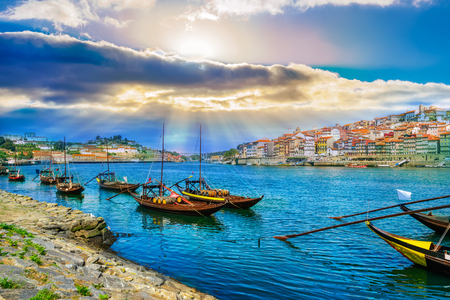 Cityscape over architecture and traditional boats on Rio Douro river in Porto city, Portugal