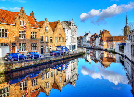 Traditional architecture along the canal, reflected in water, in Brugge city, Belgium