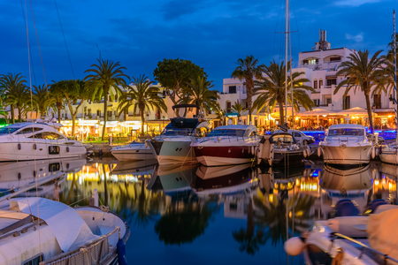 Porto Cristo in evening lights. Traditional boats illuminated at twilight in Palma de Mallorca island, Spain 新聞圖片