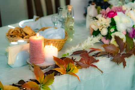 Wedding decoration with autumn leaves and candles on the table, inside the event hall