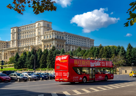 Bucharest, Romania - October 1, 2018: Touristic city-tour bus in front of Parliament Palace architecture in a sunny day. 에디토리얼