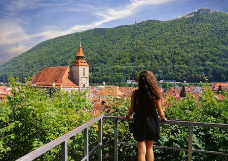 Beautiful young woman tourist enjoying the cityscape of Brasov in summer holiday
