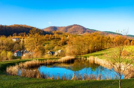 Beautiful autumn landscape with traditional houses and a lake in Sighetu Marmatiei, Maramures region - Romania