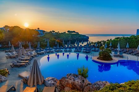 Beautiful sunrise above swimming pool resort on the coast of Mallorca island, in Cala d`Or region, Spain