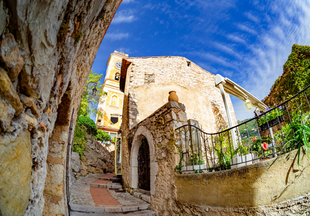 Old traditional architecture of Eze village, tower of church and the main entrance gate of the town in France 스톡 콘텐츠