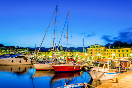 Colorful and traditional boats on Porto Azzurro port illuminated in evening lights, on the coast of Elba island in Italy