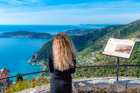 Eze, Monaco, France - Young beautiful blonde girl tourist looking towards French Riviera from the view point of Eze village in France