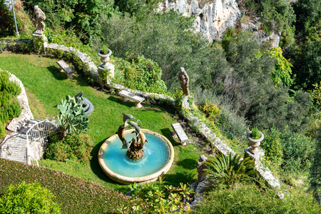 Eze, Nice, France - Beautiful traditional garden with dolphins statue playing inside artistic fountain in Eze village on Franch Riviera