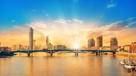 Hermosa puesta de sol sobre la ciudad de Londres con el sol iluminando los edificios y el puente de Battersea en Inglaterra