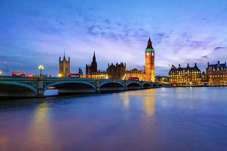 London cityscape with Big Ben and City of Westminster Abbey bridge illuminated in evening light, in England