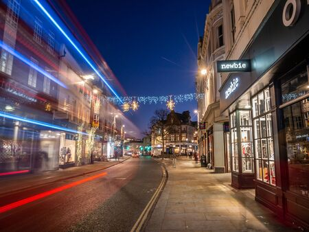 London, England, UK - December 4, 2019: Richmond street decorated with Christmas lights and car traces on the road in winter holiday season at blue hour in the morning