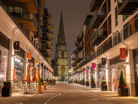 Ealing Broadway, London, UK - December 26, 2019: Downtown scene with a narrow street and the famous medieval Christchurch among city architecture illuminated at night