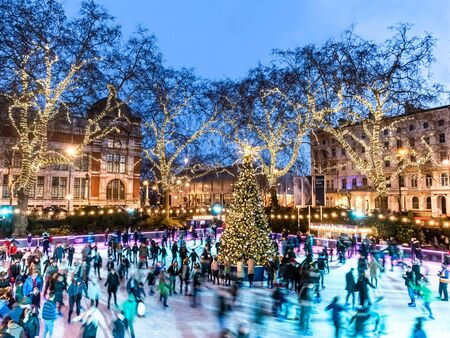 London, England, UK - December 15, 2019: People enjoyinmg ice skating outdoors in front of natural History Museum with Christmas tree and light decorations in winter holiday Editorial