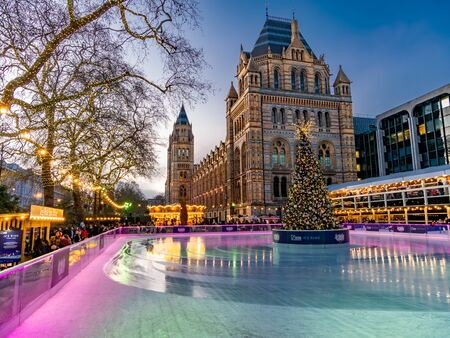 London, England, UK - December 15, 2019: Skating rink outdoors in front of natural History Museum with Christmas tree and light decorations in winter holiday