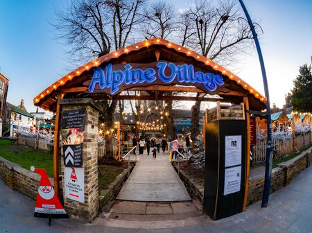 London, England, UK - December 13, 2019: Christmas Market , Alpine Village outdoors in the town square of Kingstone Upon Thames in evening lights in winter holiday time
