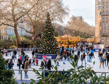 London, England, UK - December 13, 2019: People enjoying winter holiday on ice skating outdoors in front of History Museum in Christmas time Editorial