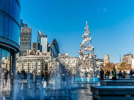 London, England, UK - November 29, 2019: Christmas tree decorated outdoors in a day time for winter holiday celebration in a beautiful town square of More London Riverside