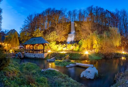 Night scene of Maramures with traditional maze mill among the river and a small waterfall in Sighetu Marmatiei - Romania
